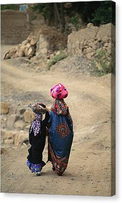 A Yemeni Woman And Child Carrying Canvas Print by Michael Melford