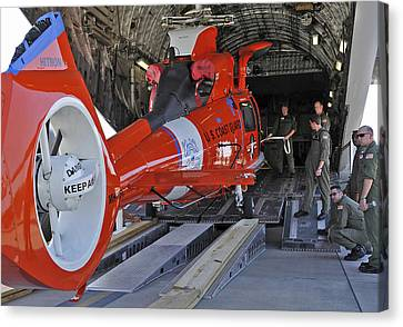An Aircrew Loads A Coast Guard Hh-65 Canvas Print by Stocktrek Images