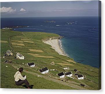 An Irishman Overlooks Cottages That Canvas Print by Howell Walker