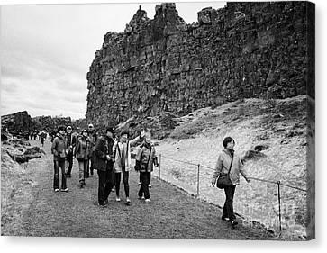 asian tourists walk through the Almannagja fault line in the mid-atlantic ridge north american plate Canvas Print by Joe Fox