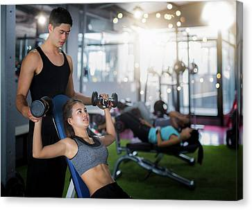 Fitness Instructor Canvas Print - Asian Trainer And Lady Take Personal Training In Fitness Club by Anek Suwannaphoom
