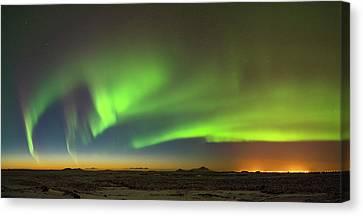 Aurora Above Keflavik In Iceland. Canvas Print by Andy Astbury