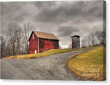 Barn In Winter Storm Canvas Print by Tony  Bazidlo