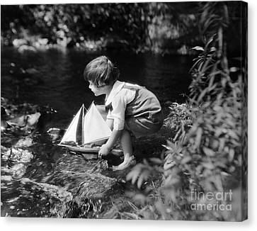 Boy Putting Toy Sailboat Into Stream Canvas Print by H. Armstrong Roberts/ClassicStock