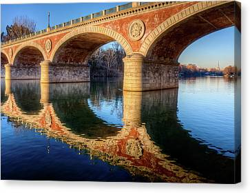 Bridge Reflection On River Canvas Print by Andrea Mucelli