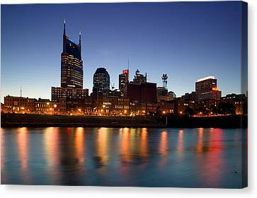 Buildings Lit Up At Dusk Canvas Print by Panoramic Images