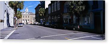 Buildings On Both Sides Of A Road Canvas Print by Panoramic Images