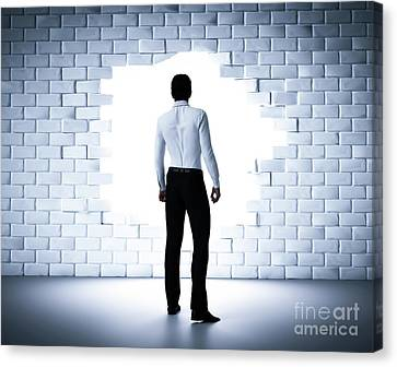 Businessman Standing Next To A Hole In A Brick Wall. Light Coming From Outside Canvas Print by Michal Bednarek
