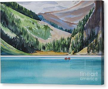 Canoeing-in-lake-louise Canvas Print by Nancy Newman