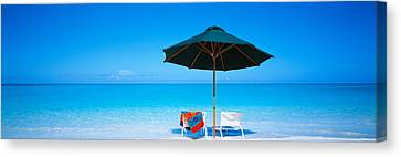 Turks And Caicos Islands Canvas Print - Chairs Under An Umbrella On The Beach by Panoramic Images