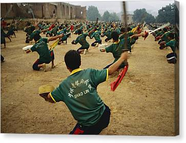 Children Practice Kung Fu In A Field Canvas Print by Justin Guariglia