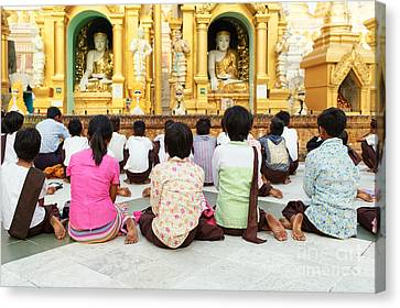 Canvas Print featuring the photograph Children Pray At Shwedagon Pagoda by Dean Harte