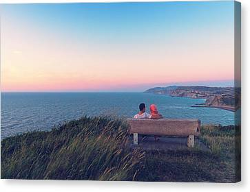 couple on bench vith view of Sopelana coast Canvas Print by Mikel Martinez de Osaba