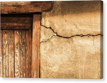Canvas Print featuring the photograph Cracked Lime Stone Wall And Detail Of An Old Wooden Door by Semmick Photo