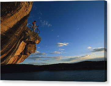 Cyclist Dan Davis Atop A Rock Overhang Canvas Print by Bill Hatcher