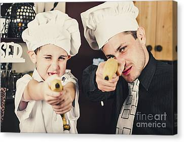 Dad And Son Cooks Shooting With Bananas In Kitchen Canvas Print by Jorgo Photography - Wall Art Gallery