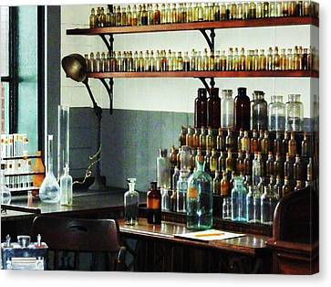 Desk With Bottles Of Chemicals Canvas Print by Susan Savad