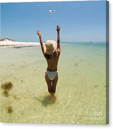 Girl On Beach Waving To Airplane Canvas Print