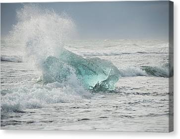 Glacial Iceberg In Beach Surf. Canvas Print by Andy Astbury