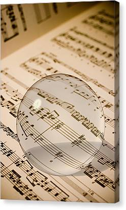 Glass Ball On Sheet Music Canvas Print by Utah Images