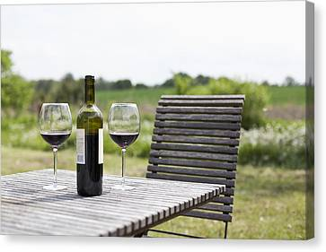 Glasses And A Bottle Of Red Wine On An Outdoor Setting Canvas Print by Halfdark