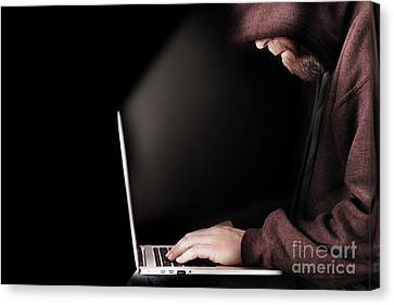 Hooded Computer Hacker Using Laptop Canvas Print