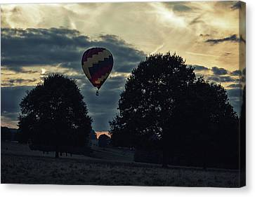 Canvas Print featuring the photograph Hot Air Balloon Between The Trees At Dusk by Scott Lyons