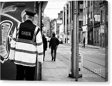 irish garda police sergeant on foot patrol in dublin city centre Ireland Canvas Print by Joe Fox