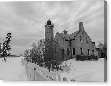 Canvas Print featuring the photograph Lighthouse And Mackinac Bridge Winter Black And White  by John McGraw