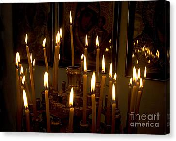 lit Candles in church  Canvas Print by Danny Yanai