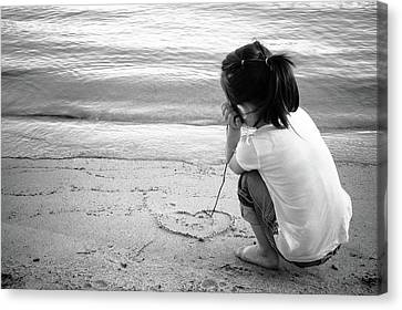 Little Girl Draws A Heart In Beach Sand With Stick Canvas Print by Bradley Hebdon