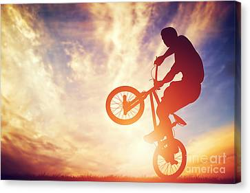 Man Riding A Bmx Bike Performing A Trick Against Sunset Sky Canvas Print