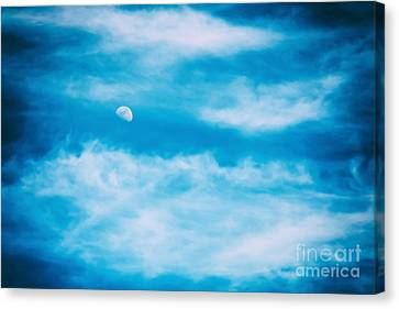 Moon Visible In Blue Sky With White Soft Clouds Canvas Print by Radu Bercan