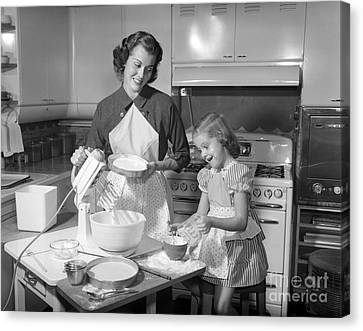 Mother And Daughter Baking A Cake Canvas Print by Debrocke/ClassicStock