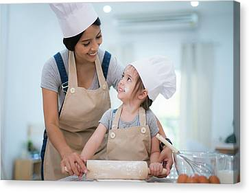 Mother And Daugthter Cooking Togather Canvas Print by Anek Suwannaphoom