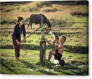 Canvas Print featuring the photograph Mother Her Sons Shower Outdoor From Groundwater Pump. by Tosporn Preede