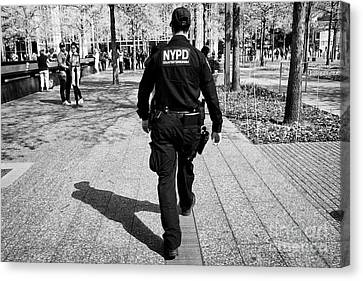 nypd counterterrorism officer walking through the 9/11 memorial plaza New York City USA Canvas Print