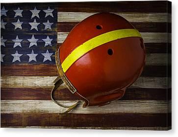 Old Football Helmet On American Flag Canvas Print by Garry Gay