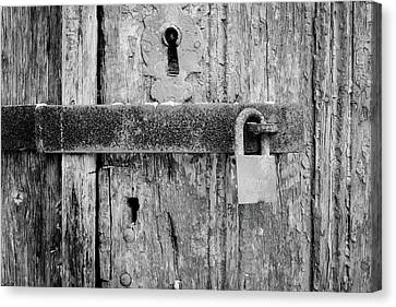 Padlock On An Old Wooden Door Canvas Print by Marco Oliveira