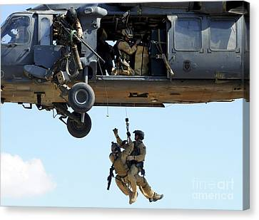 Pararescuemen Are Hoisted Into An Hh-60 Canvas Print by Stocktrek Images
