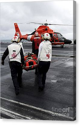 Personnel Carry An Injured Sailor Canvas Print by Stocktrek Images