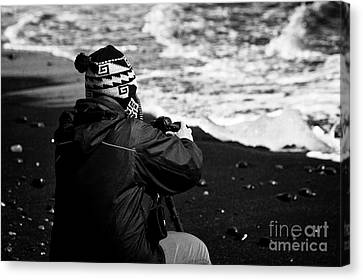 photographer taking photos of Ice washed up on black sand beach at jokulsarlon iceland Canvas Print