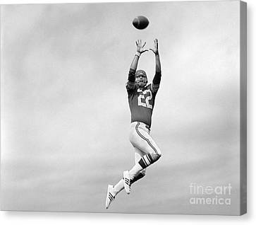 Player Jumping To Catch Football Canvas Print by H. Armstrong Roberts/ClassicStock