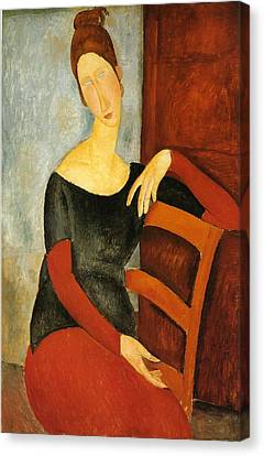 Portrait Of Jeanne Hebuterne On Red Chair Canvas Print by Amedeo Modigliani