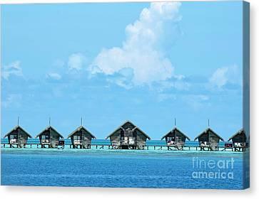 Resort Bungalows Over Sea Canvas Print by Sami Sarkis