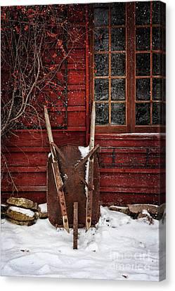 Rusty Wheelbarrow Leaning Against Barn In Winter Canvas Print by Sandra Cunningham