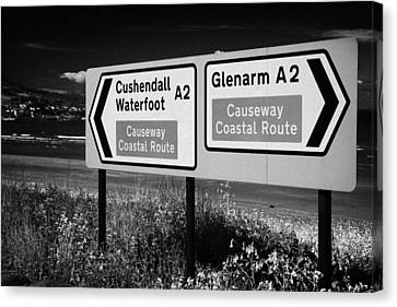 Signposts For The Causeway Coastal Route At Carnlough Between Cushendall And Glenarm County Antrim Canvas Print by Joe Fox