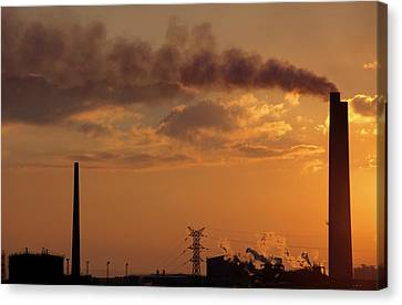 Silhouetted Smoking Chimney At Sunset Canvas Print by Sami Sarkis