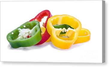 Sliced Colorful Peppers Canvas Print by Meirion Matthias