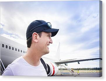 Smiling Travelling Man Standing On Airport Tarmac Canvas Print by Jorgo Photography - Wall Art Gallery